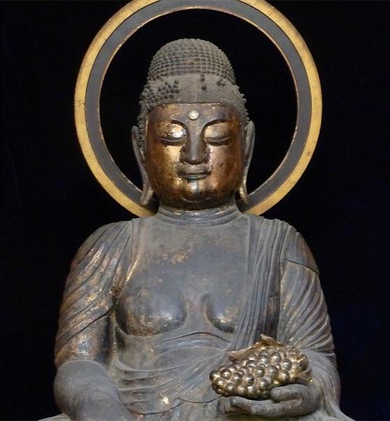 Statua di Buddha che tiene in mano un grappolo d'uva in un tempio giapponese